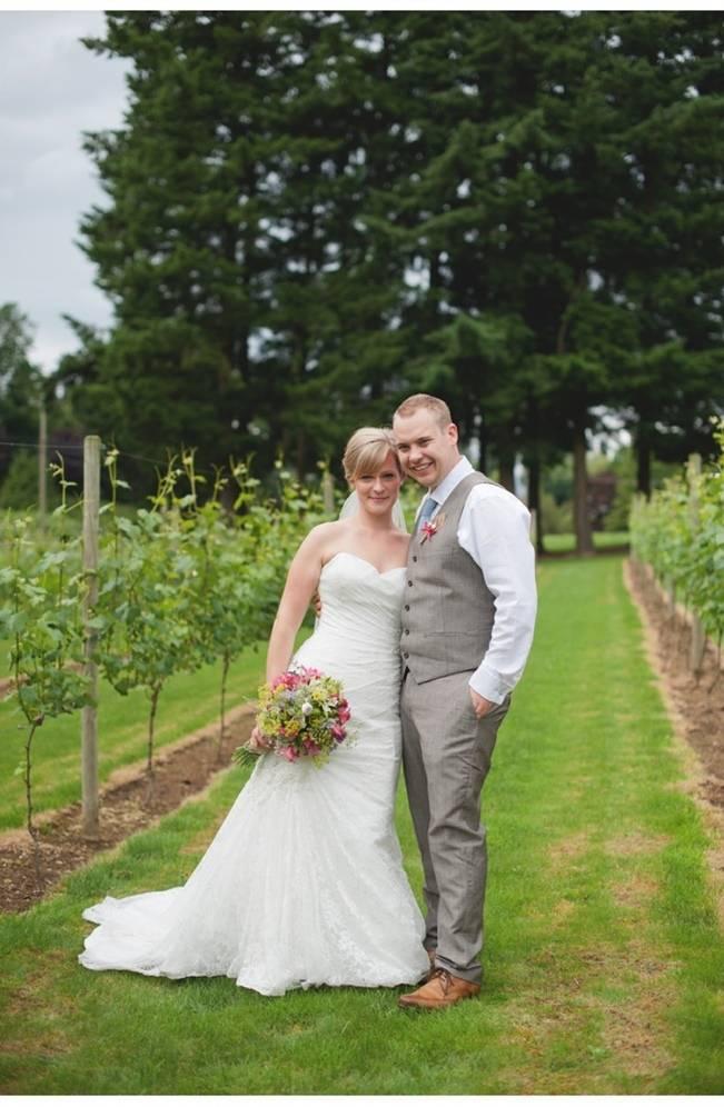 bride and groom in vineyard rows