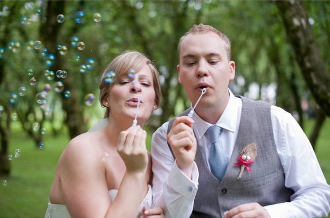 bride and groom blowing bubbles