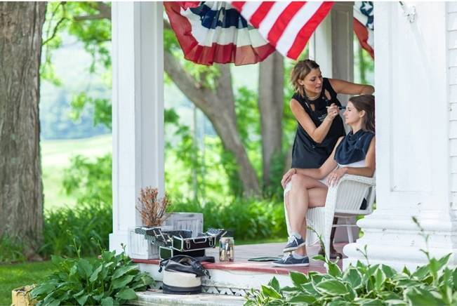 bride getting makeup done outside