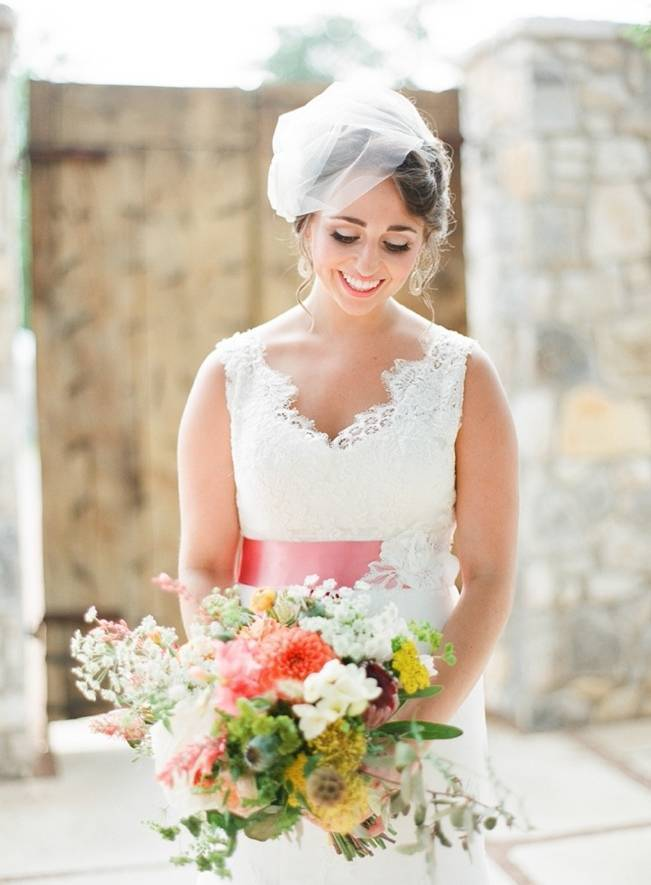 southern bride with peony bouquet and lace dress with pink sash