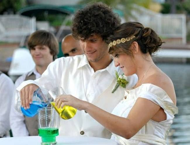 bride and groom pouring two different colors of water into one glass