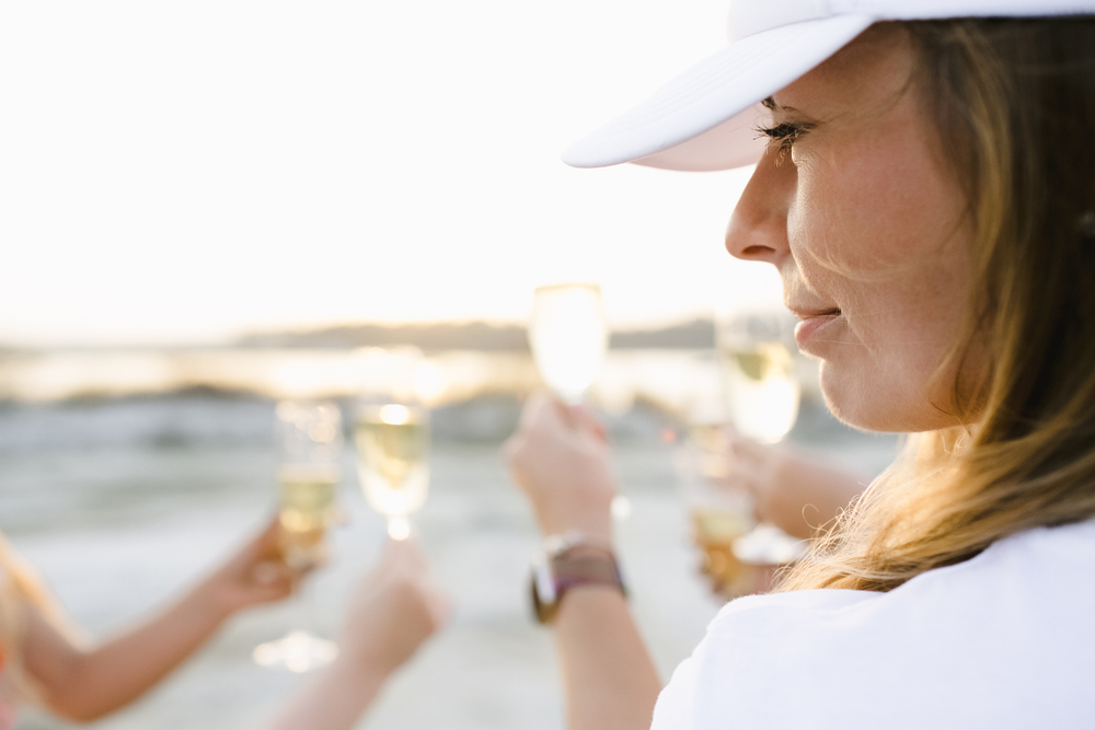 Girls clang their glasses with champagne watching the sunset